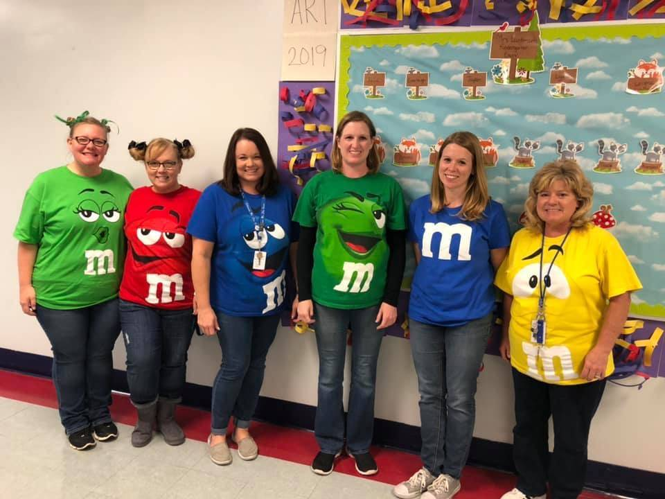 six adults dressed up as m&ms