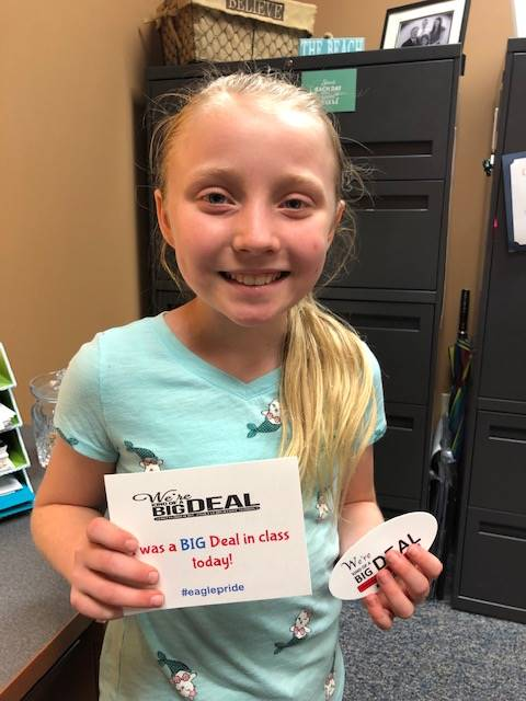 """Child smiling and holding a """"big deal"""" card"""