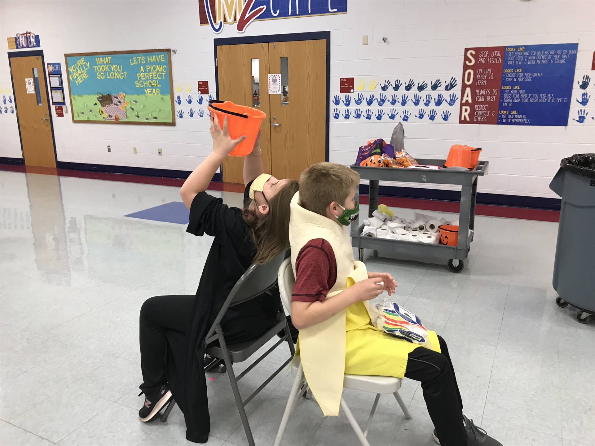 2 children playing a game with an orange bucket sitting back to back