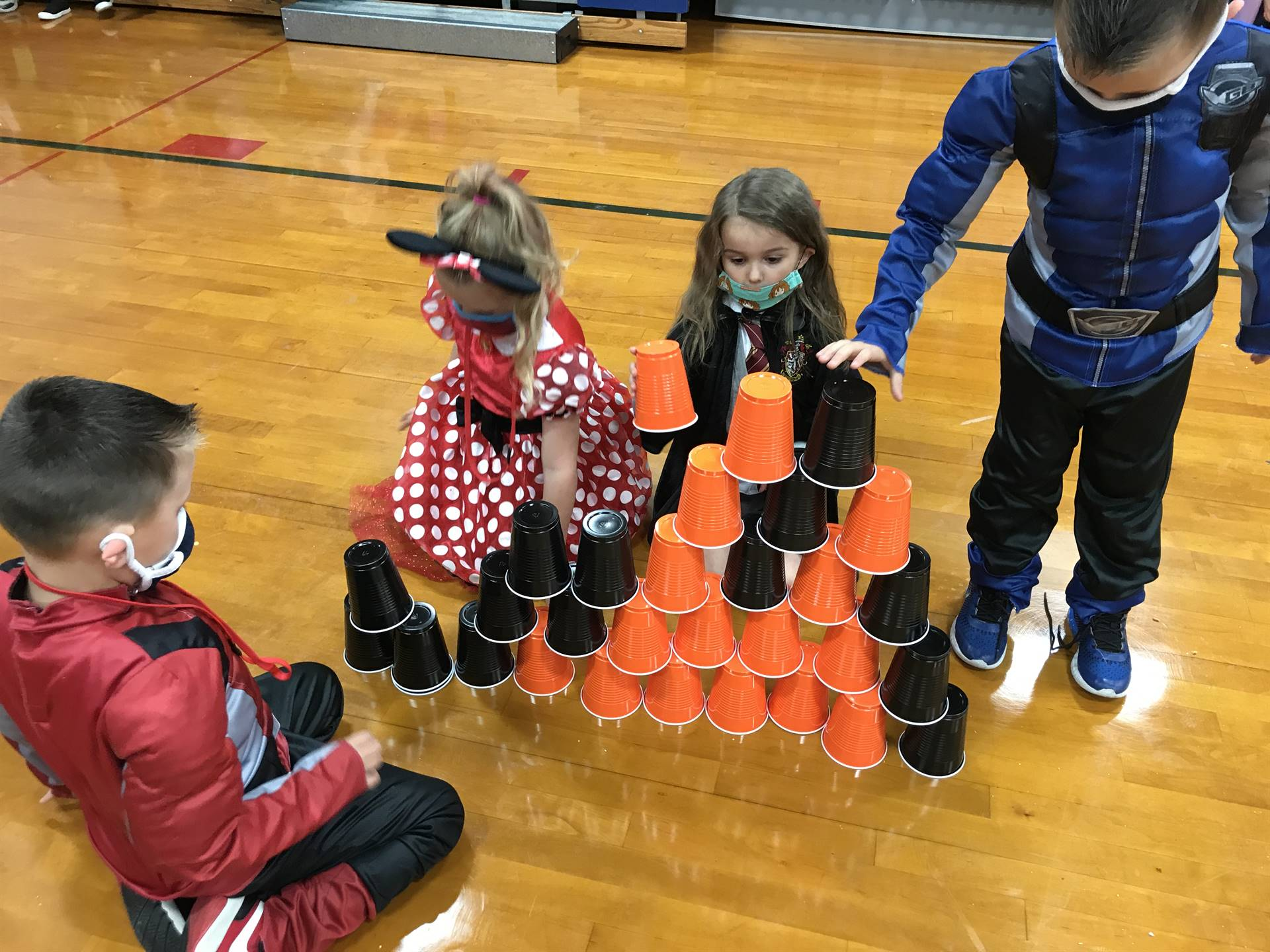4 children building a tower with orange and black cups
