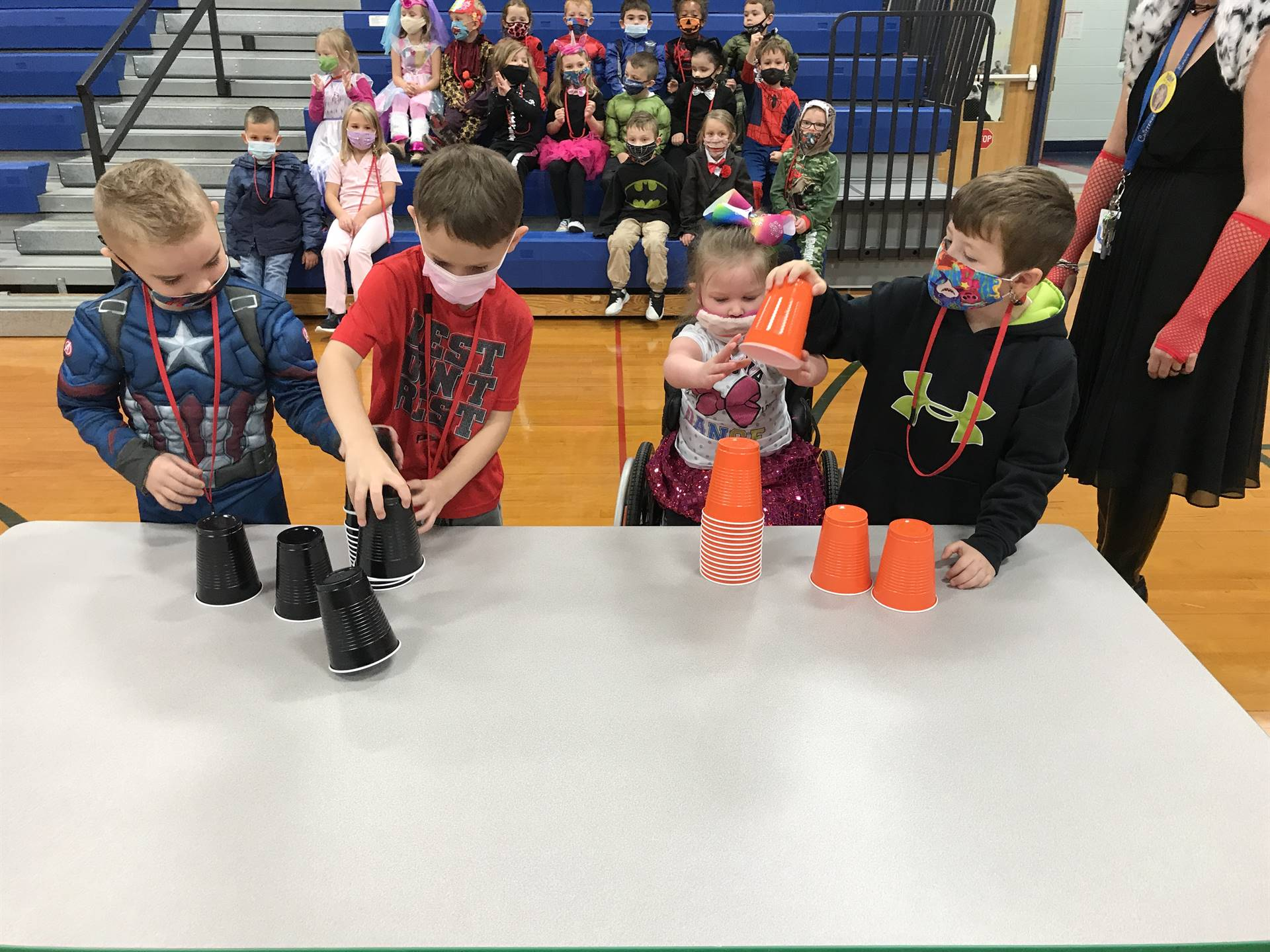 4 children building with orange and black cups on a table