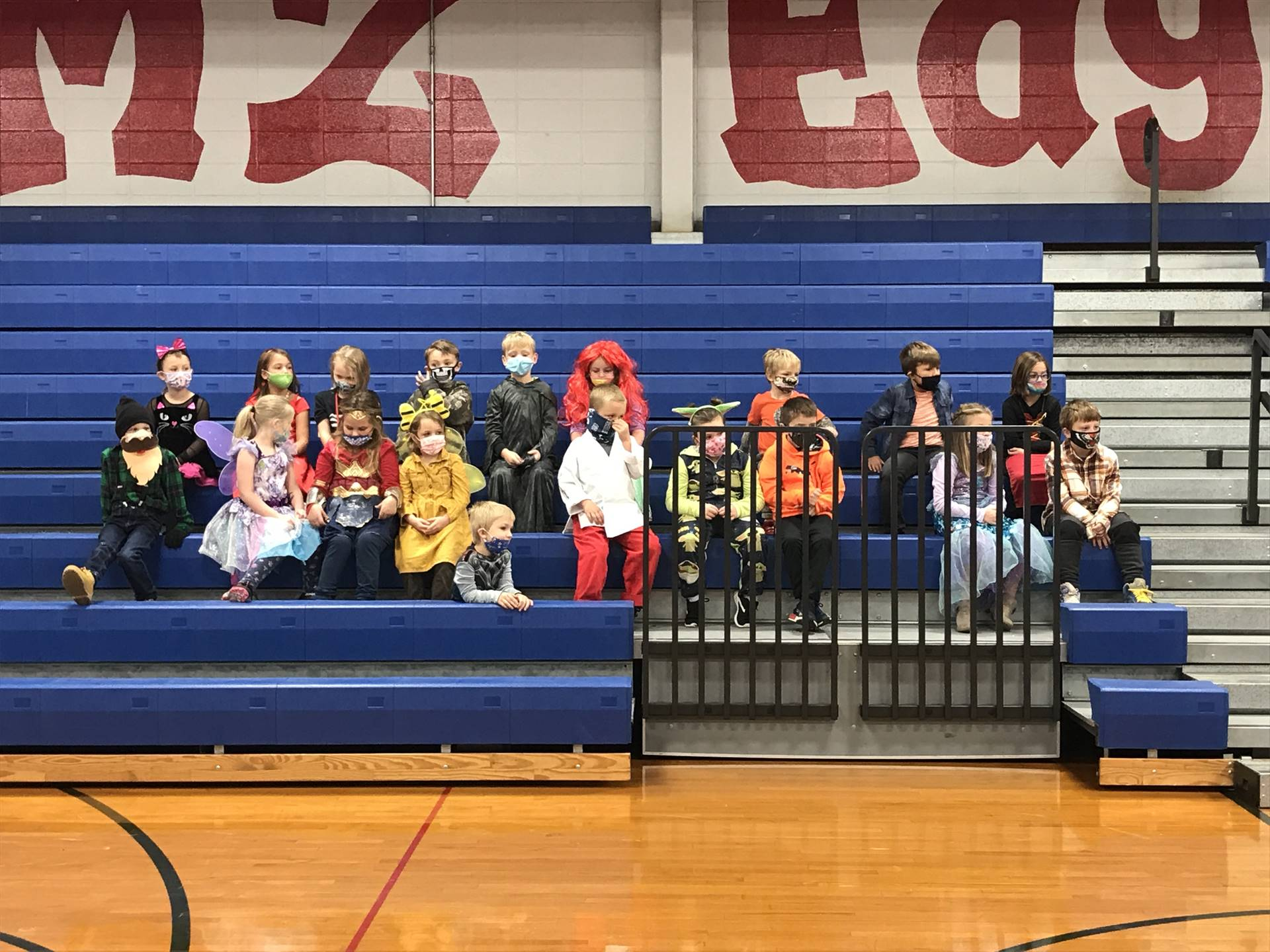 Students sitting in blue bleachers dressed up in Halloween costumes