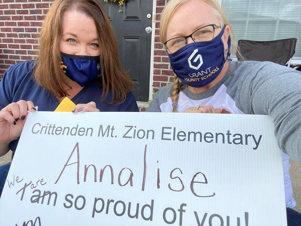 """two women with a sign that says """"Annalise we are so proud of you"""""""