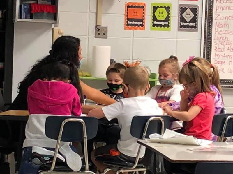 A teacher works with six students at a table