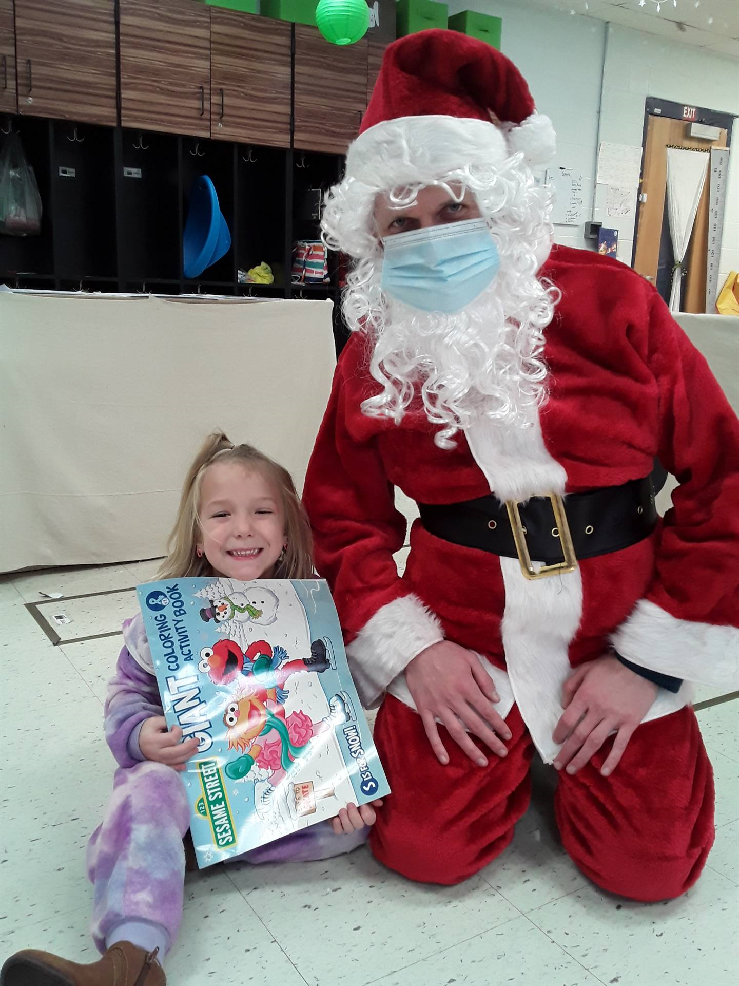 Santa Claus with a student holding a coloring book